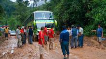 Passengers rebuild the road that had turned into a metre-deep gorge from the rain. (Ellen Keith)