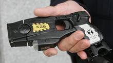 "A South Portland police officer holds a Taser X26 stun gun. Chief Bill Blair says the Toronto police force could afford to expand taser use, citing an ""opportunity"" within the proposed capital budget to pay for more of the stun guns. (HERB SWANSON/ASSOCIATED PRESS)"