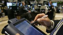 A broker uses his electronic tablet to execute trades as he works on the floor of the New York Stock Exchange Tuesday July 10, 2007