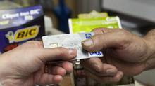A consumer pays with a credit card at a store in Montreal. Average consumer non-mortgage debt balances rose to $21,686 at the end of the third quarter, up from $21,195 in the same quarter last year, a TransUnion report says. (Ryan Remiorz/THE CANADIAN PRESS)