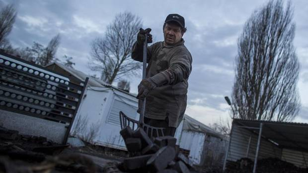 Coal delivery man Henry Schulz loads his lorry with combustible fuel in Berlin on Feb. 5, 2013. Mr. Schulz, 53, has been working as a coal delivery man for more than 30 years. (THOMAS PETER/REUTERS)