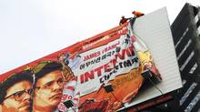 """Workers remove the poster for """"The Interview"""" from a billboard in Hollywood, California, December 18, 2014 a day after Sony announced it had no choice but to cancel the movie's Christmas release and pull it from theaters due to a credible threat. (VERONIQUE DUPONT/AFP/Getty Images)"""