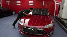 A worker cleans a Tesla Model S sedan before an event to deliver the first set of cars to customers in Beijing on April 22, 2014. (Ng Han Guan/The Associated Press)