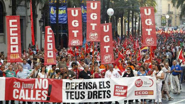 "Protesters wave flags of the General Workers Union (UGT) as they march during a demonstration against cuts in public services in central Valencia on June 20. Spain is dealing with its second recession in three years, with unemployment sitting at nearly 25 per cent. The banner reads, ""Don't keep quiet, defend your rights."" (HEINO KALIS/REUTERS)"