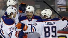 Edmonton Oilers' Jordan Eberle, centre, celebrates with teammates, left to right, Philip Larsen, Martin Marincin, and Sam Gagner, during third period NHL pre-season action against the Calgary Flames in Calgary, Alta., Saturday, Sept. 14, 2013. (CP)