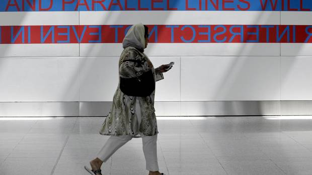 A passenger walks past Blue Republic's Delightful and Permanent Conditions of Impossibility, an installation art piece on display in Terminal 1 at Pearson International Airport, a part of Luminato, in Toronto, June 6 , 2012.