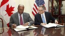 U.S. Trade Representative Ron Kirk, left, and Trade Minister Ed Fast sign the Softwood Lumber Extension Agreement in Washington in January. (KEVIN LAMARQUE/REUTERS)