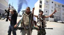 Libyan rebel fighters react as they search for snipers while fighting for the final push to flush out Moammar Gadhafi's forces in Abu Slim area in Tripoli August 25, 2011. (ZOHRA BENSEMRA/Zohra Bensemra/Reuters)