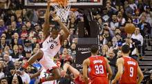 Bismack Biyombo hangs on the rim after a slam dunk against the Clippers during a game in Toronto, Sunday January 24, 2016. (Mark Blinch For The Globe and Mail)