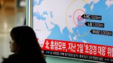 A woman walks past a television broadcasting a news report on North Korea firing ballistic missiles, at a railway station in Seoul, South Korea, on March 6, 2017. (KIM HONG-JI/REUTERS)