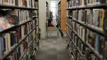 A person reads in the Vancouver Public Library, not realizing she is failing to be distracted. (Simon Hayter/The Globe and Mail)
