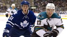 Toronto Maple Leafs Jake Gardiner (L) and San Jose Sharks Torrey Mitchell race for the puck into the end boards during the first period of their NHL hockey game in Toronto February 23, 2012. (FRED THORNHILL/REUTERS)