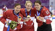 Team Canada's Jayna Hefford, Haley Irwin and Gillian Apps show off their gold medals after defeating Team USA in the womens gold medal hockey game at the Sochi Winter Olympics (Paul Chiasson/THE CANADIAN PRESS)