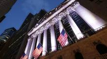 In this Oct. 8, 2014 photo, American flags fly in front of the New York Stock Exchange, in New York. Global stock markets swung higher Thursday, Jan. 15, 2015 led by a surge in Chinese shares, extending a volatile pattern of sharp sell-offs and rousing gains as investors second guess uncertain prospects for the world economy. (Mark Lennihan/AP)