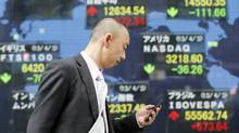 A pedestrian passes an electronic stock board of a securities firm in Tokyo showing Japan's benchmark Nikkei 225 stock index, centre top, that gained 272.34 points to 12,634.54 after the central bank announced more monetary easing. (Koji Sasahara/AP)