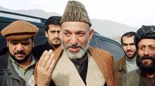 Accompanied by Defense Minister Mohammad Fahim, left, Hamid Karzai, center, interim prime minister of the Islamic Republic of Afghanistan, who will take power Dec. 22, greets a crowd of Afghan people on the road from Kabul to Jebal Saraj on his way to pray at the grave of slain opposition leader Ahmad Shah Massood in Bazarak district, 120 km (74 miles) north of the Afghan capital Kabul on Friday, Dec. 14, 2001. Left: Mohammad Fahim, Defense Minister of the Islamic Republic of Afghanistan.(AP Photo/Marco Di Lauro) (MARCO DI LAURO/Associated Press)