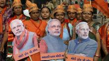 Supporters of India's main opposition Bharatiya Janata Party hold placards of their prime ministerial candidate Narendra Modi during a rally to file his nomination for the upcoming general election in Vadodara on April 9, 2014. (AJIT SOLANKI/ASSOCIATED PRESS)
