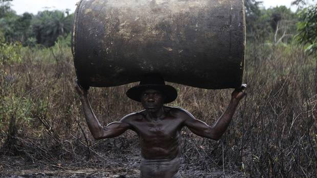 Ebiowei, 48, carries an empty oil container on his head to be filled with refined fuel at an illegal refinery site near the Nun River in Nigeria's oil state of Bayelsa, Nov. 27, 2012. (AKINTUNDE AKINLEYE/REUTERS)