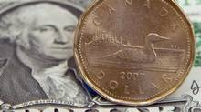 A Canadian dollar, or loonie, sits on top of its American counterpart in Toronto on Sept. 20, 2007. (Adrian Wyld/CANADIAN PRESS)
