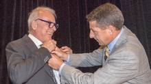 Couche Tard founder and chairman Alain Bouchard (left), gets help with his microphone from chief executive Brian Hannasch before the start of the company's annual meeting, Tuesday, September 20, 2016 in Laval, Quebec. (Ryan Remiorz/THE CANADIAN PRESS)