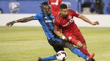 The Montreal Impact and Toronto FC split their two MLS meetings this season, with each winning in the other's stadium. They meet a third time this Sunday at Montreal's Saputo Stadium. Montreal Impact forward Dominic Oduro, left, slides into Toronto FC defender Justin Morrow during second half Amway Canadian Championship semifinal action Wednesday, June 8, 2016 in Montreal. THE CANADIAN PRESS/Paul Chiasson (Paul Chiasson/THE CANADIAN PRESS)