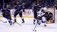 Minnesota Wild centre Martin Hanzal reaches for the puck as three St. Louis Blues players look on Wednesday night in St. Louis, Mo. (Jeff Curry/USA Today Sports)
