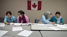 Mina, Marijam, Horia and Farida (L-R), all from Afghanistan, take part in a Canadian citizenship class Jun 28, 2012 at the Afghan Women's Organization in Toronto. (Moe Doiron/The Globe and Mail)