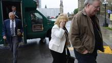 An unidentified man shields Sen. Pamela Wallin from media cameras as she arrives at the Senate entrance on Parliament Hill in Ottawa, June 6, 2013. (Sean Kilpatrick/THE CANADIAN PRESS)