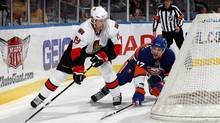 Jason Spezza of the Ottawa Senators controls the puck against Andrew MacDonald of the New York Islanders on February 14, 2010 at Nassau Coliseum in Uniondale, New York. (Jim McIsaac/2010 Getty Images)