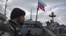 A Russian flag is raised aboard a Ukrainian navy ship that is next to the Ukrainian corvette Pridniprovya, right, in Sevastopol, Crimea, Thursday, March 20, 2014. As the U.S. levies punitive banking restrictions against Russia, sources say Ottawa is also considering sanctions against firms. (Andrew Lubimov/AP)
