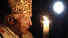Pope Benedict XVI holds a tall, lit candle as he enters the darkened St. Peter's Basilica in the Vatican on Saturday. (Pier Paolo Cito/Associated Press)