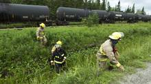 Firefighters in Nantes, Que., inspect a row of oil tankers sitting on a railway siding on July 10, 2013. This is where the train that crashed and burned in nearby Lac-Mégantic originated. (PETER POWER/THE GLOBE AND MAIL)