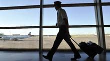 An Air Canada pilot walks to his plane at the International airport in Calgary, September 20, 2011. Air Canada on Friday warned travellers of flight disruptions, saying some pilots are staging an illegal walkout. (© Todd Korol / Reuters/REUTERS/Todd Korol)