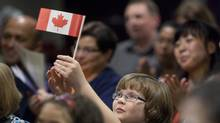 Emily Hughes, 9, holds up a Canadian flag during a Canadian Citizenship ceremony in Ottawa on Sept. 29, 2010. Hughes along with her parents came from England to Canada in 2005. (Pawel Dwulit/Pawel Dwulit for The Globe and Mail)