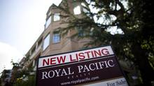 A for-sale sign rests on the lawn of a condo building in downtown Vancouver (Rafal Gerszak For The Globe and Mail)