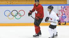 Team Canada captain Sidney Crosby gabs with forward Martin St. Louis, a last-minute injury replacement for Steven Stamkos, during Monday's practice. St. Louis was a standout in the first skate. (Julie Jacobson/AP)