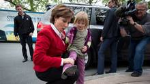 B.C Liberal Leader Christy Clark admires five-year-old Taylor Abramson's pink cowboy boots at a campaign stop in Ladner, B.C., on Monday, May 13, 2013. (THE CANADIAN PRESS/DARRYL DYCK)