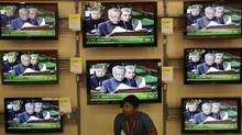 An Indian man sits in front of television screens broadcasting coverage of Indian Finance Minister Pranab Mukherjee as he reads out the budget, at a store in Bhubaneswar, India, Friday, March 16, 2012. (Biswaranjan Rout/AP)