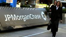 Pedestrians walk past the JPMorgan Chase headquarters in New York. JPMorgan kicks off U.S. banks' earnings season when it reports on Oct. 13, 2011. (DON EMMERT/AFP/Getty Images)