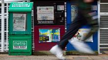 A man runs past newspaper boxes in downtown Vancouver, B.C., on Thursday March 29, 2012. (DARRYL DYCK For The Globe and Mail)