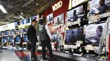 In this Feb. 3, 2010 file photo, a shopper listens to a salesclerk in front of flat-panel TVs at an electronics store in Tokyo. Japan's economy stumbled in the last three months of the year, contracting for the first time in five quarters. Gross domestic product shrunk at an annualized rate of 1.1 percent in the October-December period, the government said Monday Feb. 14, 2011. (Shizuo Kambayashi/AP/Shizuo Kambayashi/AP)