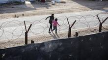 Nawal and Amani run towards their prefabricated home at Zaatari Syrian refugee camp in Jordan on Nov. 30, 2015. Zaatari was one of the refugee camps visited by Immigration Minister Ahmed Hussen during his trip to the Middle East. (Annie Sakkab For The Globe and Mail)