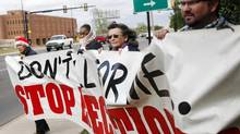 Protesters hold a banner during a demonstration at the governor's mansion in Oklahoma City on April 29, 2014, over the planned execution of two inmates. An execution that used a new drug combination left an Oklahoma inmate writhing and clenching his teeth on the gurney later Tuesday, leading prison officials to halt the proceedings before the inmate's eventual death from a heart attack. (KT KING/ASSOCIATED PRESS)