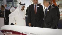 Sheikh Ahmed bin Saeed Al Maktoum, chairman of Emirates Airlines, shakes hands with Boeing Commercial Airplanes chief executive Ray Conner (front right) as Boeing chairman James McNerney (second left) looks on during the Dubai Airshow, Nov. 18, 2013. (Caren Firouz/Reuters)