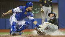 Pittsburgh Pirates' Adam Frazier, right, is tagged out at home by Toronto Blue Jays catcher Russell Martin during fifth inning preseason MLB baseball action, in Montreal on Friday, March 31, 2017. (Paul Chiasson/THE CANADIAN PRESS)