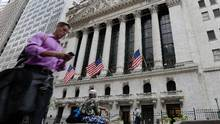A man passes the New York Stock Exchange, Friday, June 24. (Richard Drew/AP)