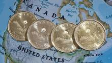 Canadian dollar coins, or loonies, are displayed on a map of North America (Paul Chiasson/THE CANADIAN PRESS)