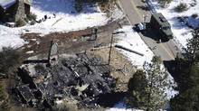 Authorities stand at a burnt-out cabin near Angelus Oaks, Calif., where police engaged in a shootout with fugitive former Los Angeles police officer Christopher Dorner on Tuesday. (Reuters)