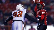 Calgary Stampeders' quarterback Kevin Glenn (R) throws a pass while BC Lions' Maurice Evans comes in for the late tackle during the first half of their CFL game in Calgary, Alberta, October 26, 2012. (TODD KOROL/REUTERS)