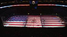 An American flag lights up the rink in the Pepsi Center during the singing of the national anthem (file photo). (DAVID ZALUBOWSKI/AP)